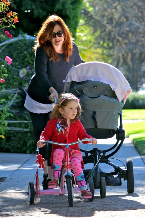 Alyson Hannigan pushes her baby daughter Keeva in a stroller while older girl Satyana rides her bicycle